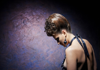 The woman with a beautiful hairdress against a dark background