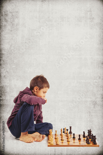 Kid (6 year old) playing chess, isolated on grunge background