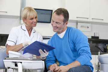 A female dentist discussing dental records with her male patient