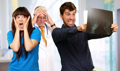 Young Couple Watching X-ray In Front On Frustrated Doctor