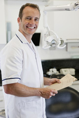 A male dentist holding patient dental records