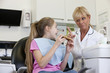 A young girl at the dentist eating a giant cookie