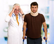 Young Man Wearing Cervical Collar And Frustrated Doctor Behind I