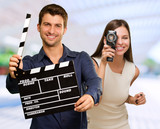 Man Holding Clapper Board And Woman Capturing Photo