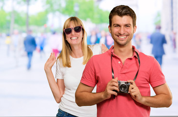 Man Holding Camera In Front Of Woman