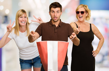 Man Holding Shopping Bag In Front Of Two Happy Women
