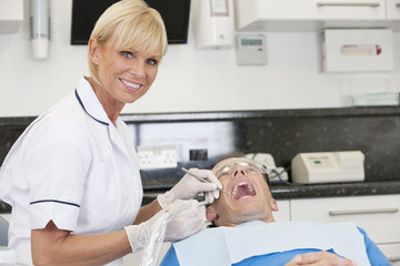 A female dentist treating her male patient