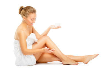 young woman in towel terry puts cream on legs