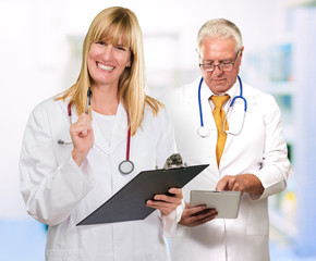 Two Happy Doctors While Holding Clipboard, Tablet