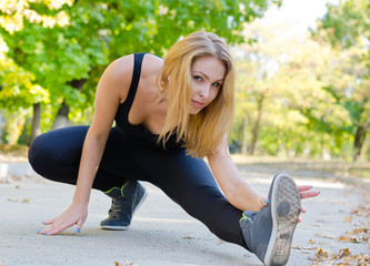 Blond girl stretching wearing a black leotard