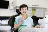 A young boy at the dentist holding a giant cookie