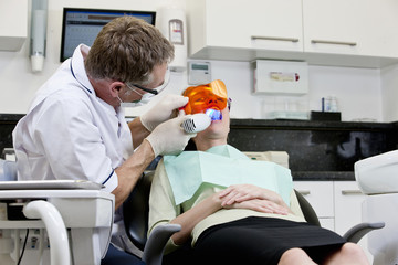A male dentist filling a female patients teeth