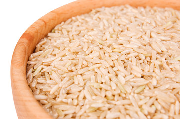 Raw brown rice in wooden bowl close-up over white background