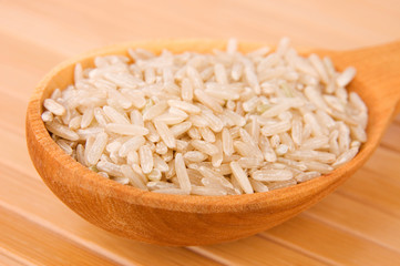 Raw brown rice in wooden spoon on bamboo close-up
