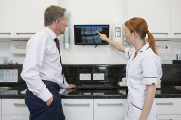 A female dentist showing an x-ray to a male patient