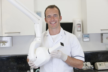 A male dentist holding an x-ray machine