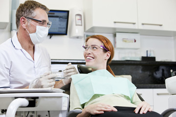 A male dentist talking to a female patient