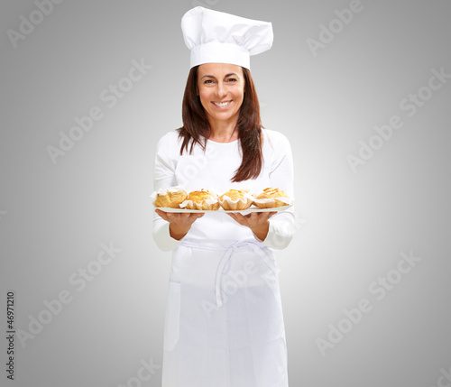 Woman chef holding baked food - 46971210