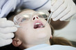 A young girl having her teeth examined by a dentist, close up