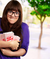 Portrait Of Young Woman Holding Popcorn Container
