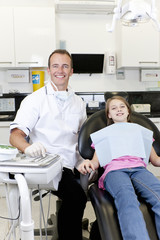 A male dentist with a young girl patient