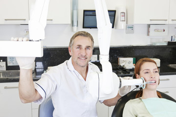 A male dentist taking an x-ray of a female patients teeth