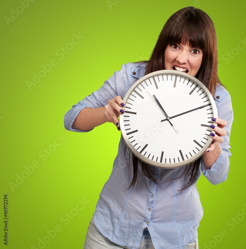 A Young Girl Holding A Clock And Angry