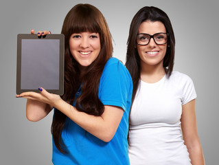 Two Happy Woman Holding Ipad