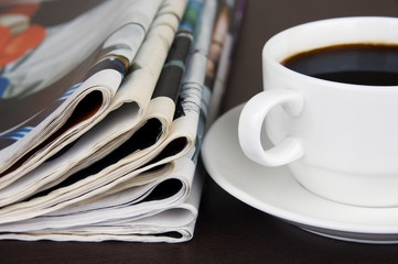 Take a break: pile of newspapers and cup of coffee on the table