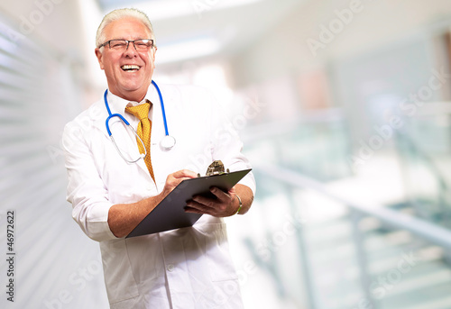 Happy Male Doctor Writing On Clipboard