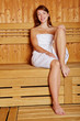 Frau sitzt lächelnd in Sauna