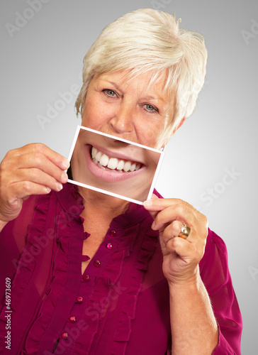Senior Woman With Manifying Glass Showing Teeth