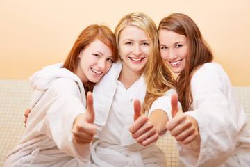 Frauen im Bad halten Daumen hoch