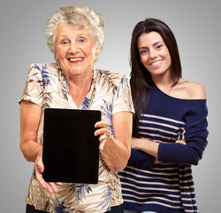 Senior Woman Holding Digital Table In Front Of Young Woman