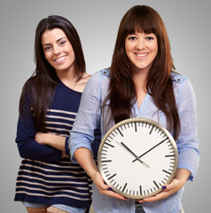 Portrait Of Happy Women Holding Clock