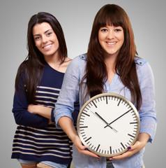 Portrait Of Happy Women Holding Clock