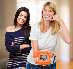Young Woman Gesturing In Front Of Happy Woman
