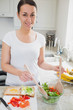 Young woman tossing salad for sandwich