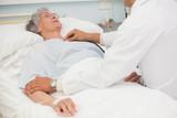 Doctor listening to heart beat of elderly patient