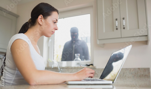 Young woman seeing reflection of robber