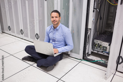 Man sitting beside servers with laptop