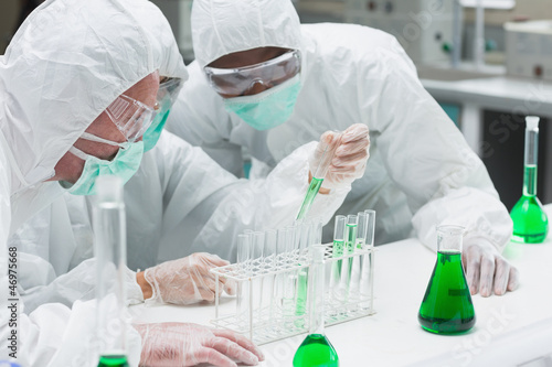 Two chemists experimenting with the green liquid
