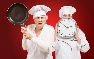 Two Female Chef Holding Saucepan And Clock