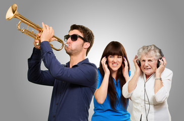 Young Man Blowing Trumpet  And Women Getting Irritation Wearing
