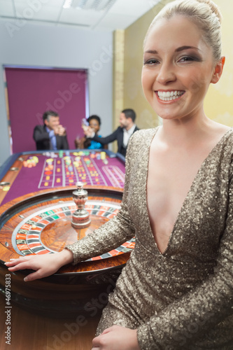 Woman smiling beside roulette wheel