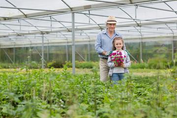 Gardener and grandchild holding a flower