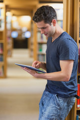 Man leaning against book shelf using tablet pc