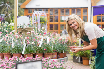 Smiling florist looking at clay pots