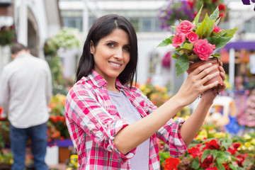 Smiling woman lifting a flower pot