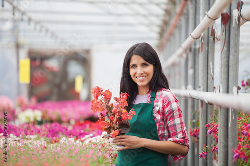 Woman holding a flower working in a greenhouse